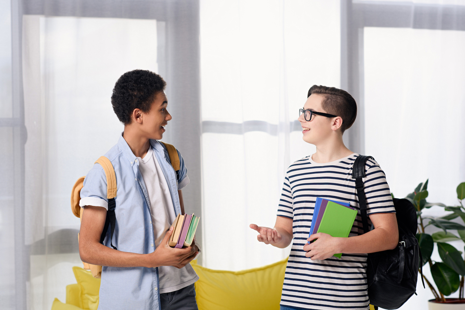 multicultural teen boys holding books and talking at home